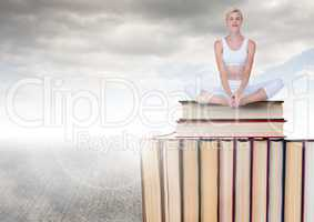 Woman meditating  sitting on Books stacked by grey cloudy sky