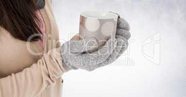 Close up of woman holding polka dot mug against white wall