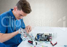 Man with electronics against grey wall