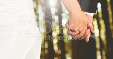 Wedding couple holding hands in forest woods