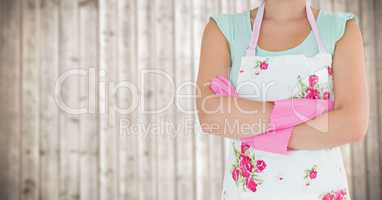 Woman in apron with arms folded against blurry wood panel