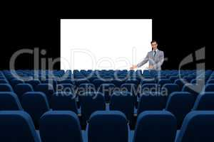 Businessman presenting at blank board in front of 3d empty chairs