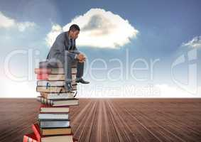 Businessman sitting on Books stacked by blue cloudy sky