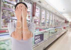 Sad woman grief hands over face against supermarket background
