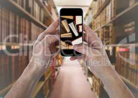 Hand with phone showing standing books against blurry bookshelves