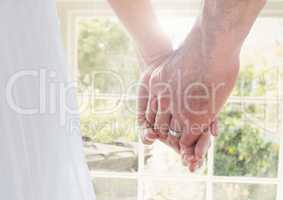 Wedding coupe holding hands by window
