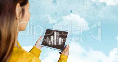 Woman with tablet showing white buildings against sky with clouds