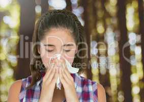 Young woman with hayfever blowing nose in forest trees