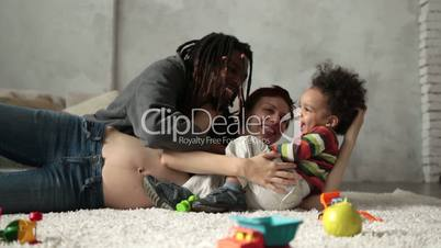 Interracial family with child playing on the floor