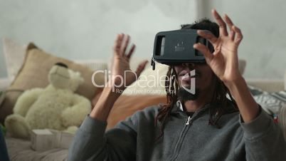 Excited man using virtual reality goggles at home