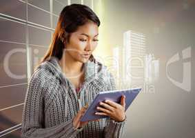 Woman with tablet and white building graphic against window evening sky