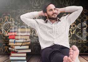 Man sitting relaxed with Books stacked by antique wallpaper decorative