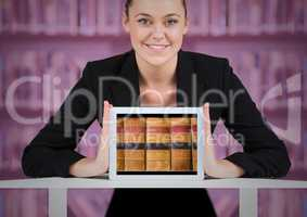 Business woman with tablet showing book spines against blurry bookshelf with pink overlay