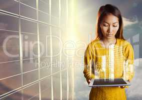 Woman looking down at tablet and white building graphic against window and evening sky