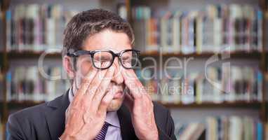 Business man rubbing eyes against blurry bookshelf
