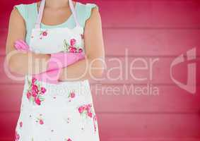 Woman in flowery apron with arms folded against blurry pink wood panel