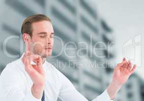 Businessman Meditating by office buildings