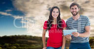 Couple with tablet with flare against sky and hills