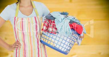Woman in apron with laundry against blurry yellow wood panel