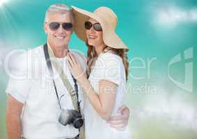 Couple in summer clothes against blue green background with clouds and flare