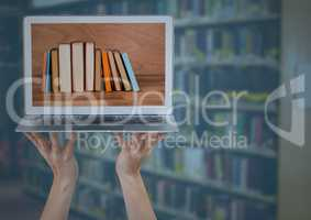 Hands with laptop showing book spines against blurry bookshelf with blue overlay