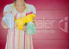 Woman in apron with arms folded and cleaner against blurry pink wood panel
