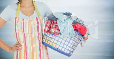 Woman in apron with laundry against blurry grey wood panel