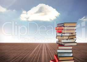 Books stacked by blue cloudy sky