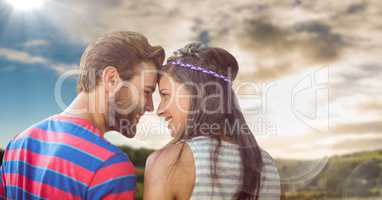 Hippie couple with flare against sky and hills