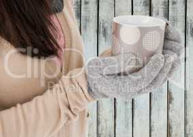 Close up of woman holding polka dot mug against wood panel