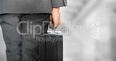 Business person legs with brief case against blurry grey stairs