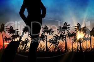 Silhouettes of lady with suitcase against sunset view with palm trees