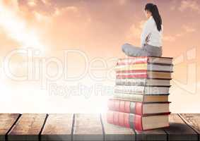 Businesswoman sitting on Books stacked by sunny clouds