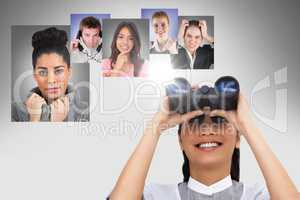 Smiling woman looking at flying portraits of business people with binocular