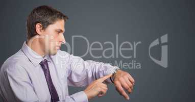 Man in lavender shirt looking at watch against grey background