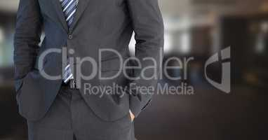 Business man mid section with hands in pockets in blurry room