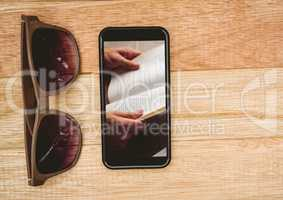 Sunglasses and phone showing open book