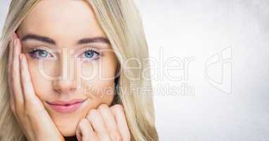 Close up of woman with hand on face against white wall