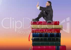 Businessman sitting on Books stacked by twilight sky