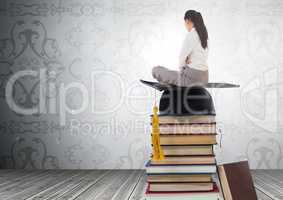 Woman sitting on Books stacked by decorative wallpaper with graduation hat