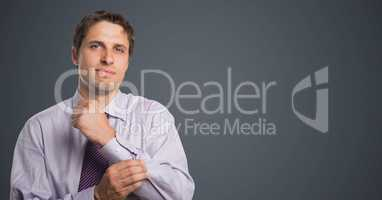 Man in lavender shirt holding arm against grey background