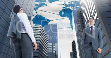 Businessmen looking up in tall City with world map and people networks