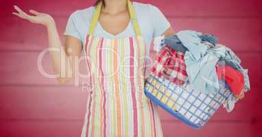 Woman in apron with laundry against blurry pink wood panel