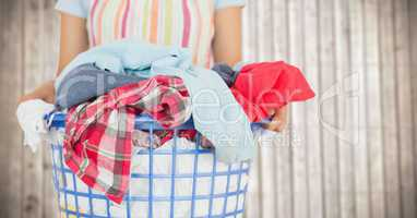 Woman in apron with laundry against blurry wood panel