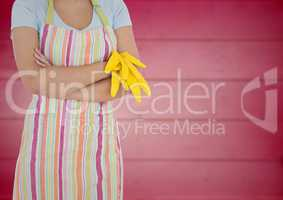 Woman in apron with arms folded and gloves off against blurry pink wood panel