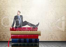 Man sitting on Books stacked by rustic wallpaper
