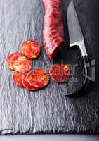 Spanish chorizo with a knife on a stone plate.