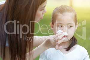Flu season, little girl blowing nose.