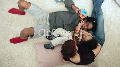 Top view of positive parents with child relaxing