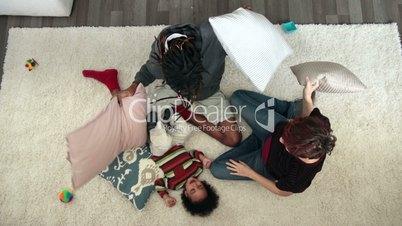 Joyful family having pillow fight on the floor